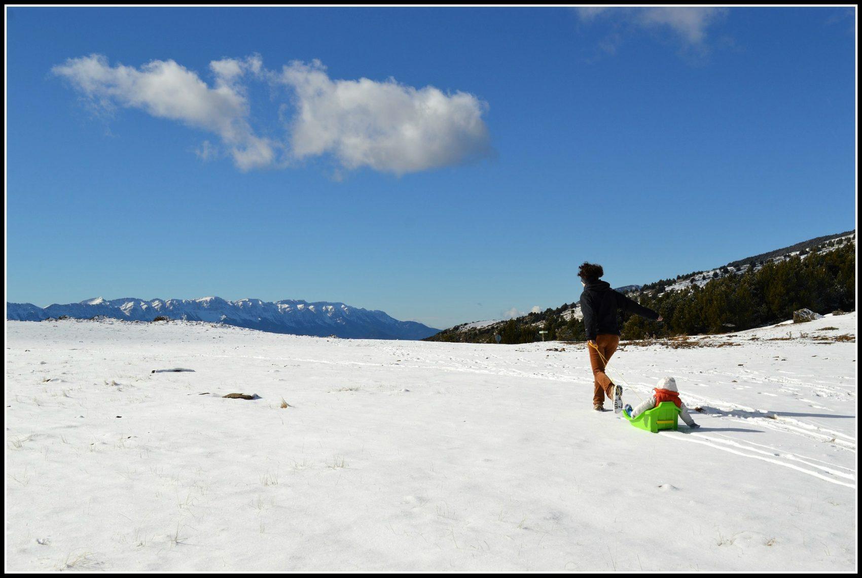 family at ski resort playing toboggan