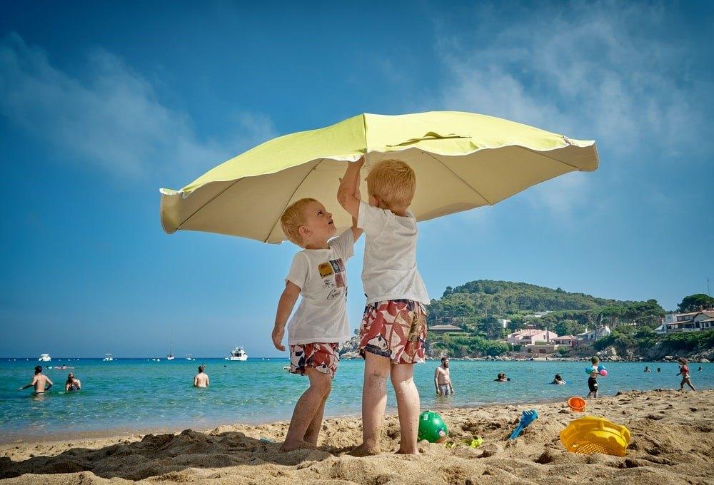 kids at beach under umbrella
